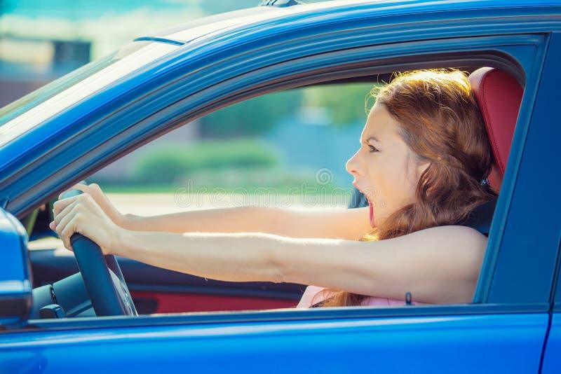 Missnöjd ilsken skitförbannad aggressiv kvinna som kör bilen som ropar att skrika fotografering för bildbyråer