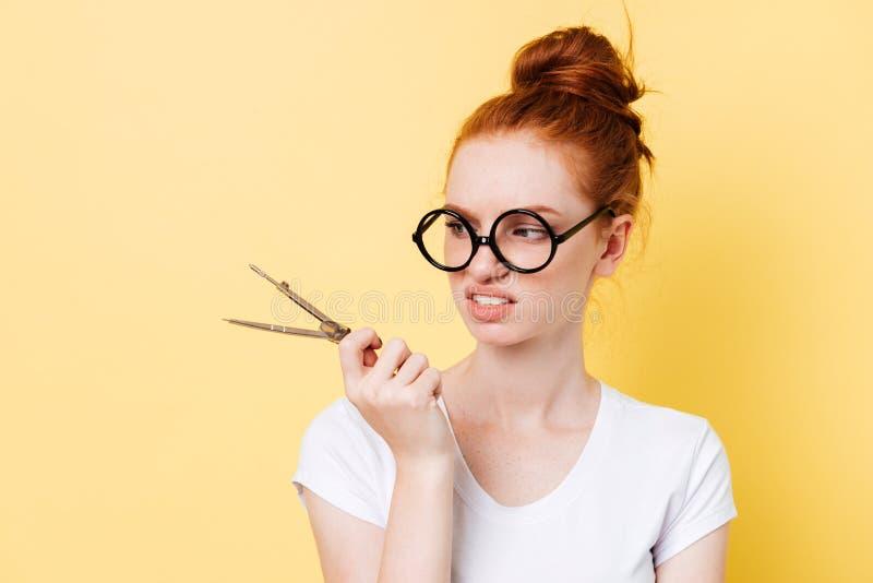 Missnöjd ljust rödbrun kvinna i glasögon som ser på avdelare royaltyfria foton