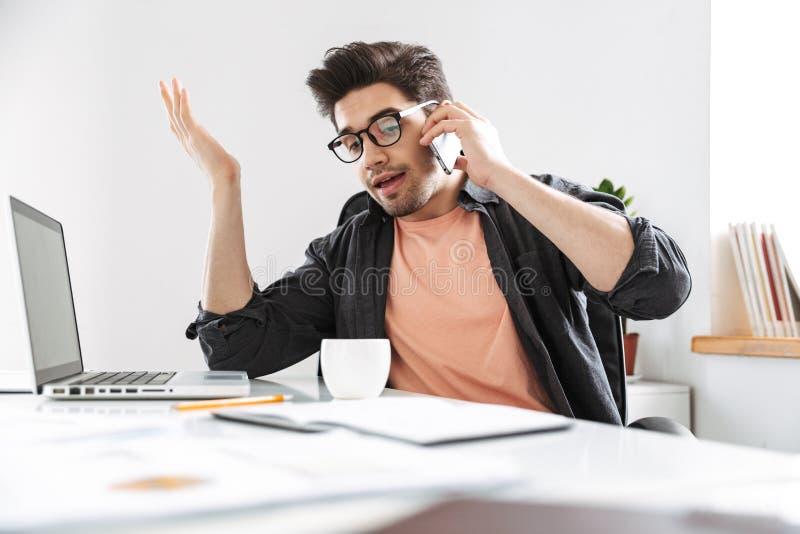 Missnöjd stilig man i glasögon som talar vid smartphonen royaltyfria bilder
