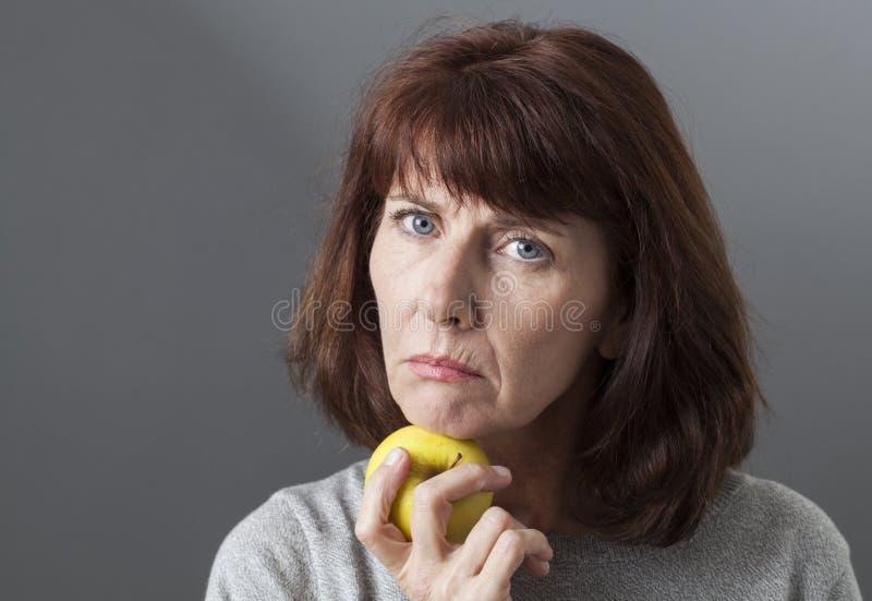 Missnöjd 50-talkvinna som tänker om hud som åldras med symbol av den sunda livsstilen och ny mat i hand royaltyfria bilder