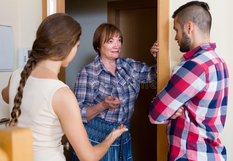 Missnöjda grannar som argumenterar i dörröppningen arkivbild