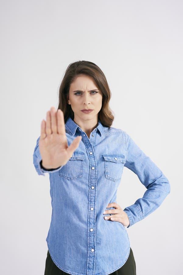 Missnöjt tecken för kvinnavisningstopp på studioskottet fotografering för bildbyråer