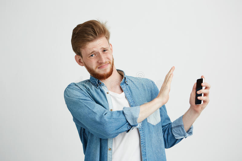 Missnöjt ungt stiligt tecken för manvisningstopp att ringa i en annan hand som ser kameran som motstår över vit arkivbild
