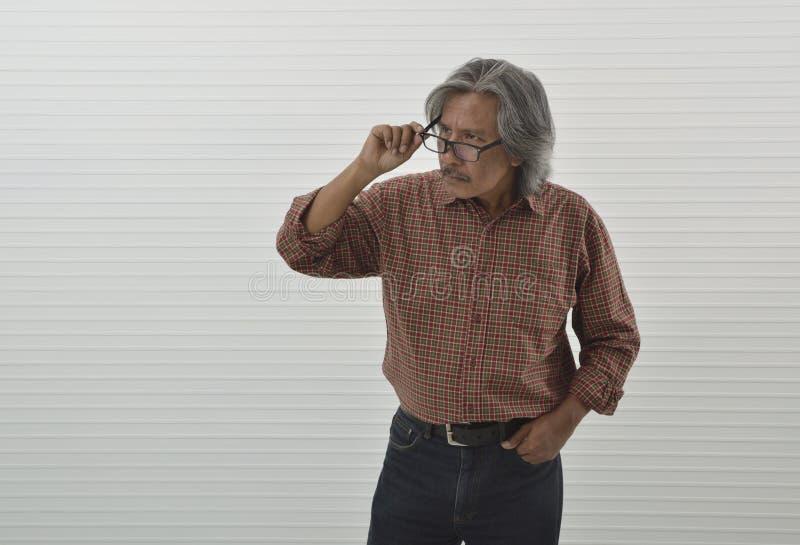 Misstänksam asiatisk hög affärsman i röd tillfällig skjorta och blått royaltyfri bild