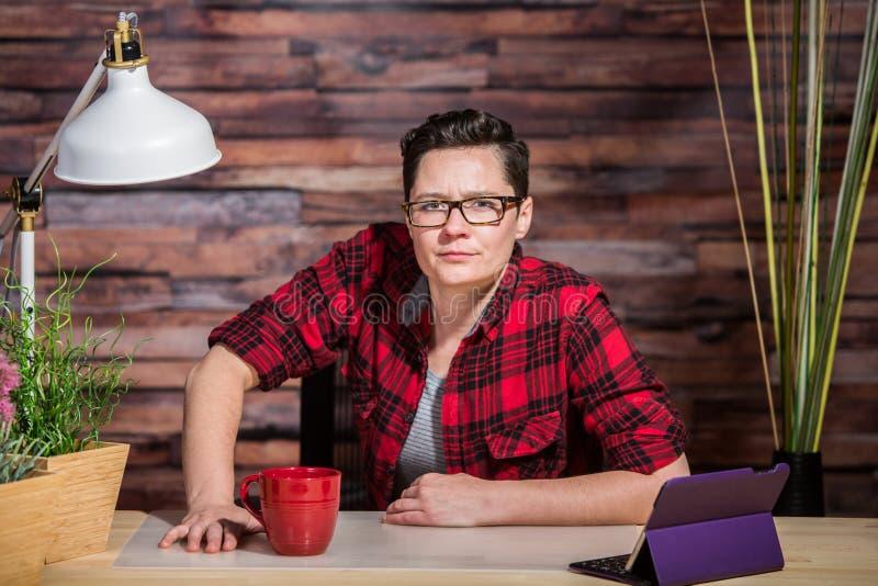 Misstänksam kvinna på skrivbordet arkivbilder