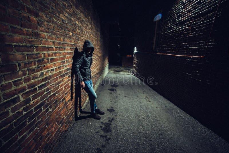 Misstänksam man i den mörka gränden som väntar på något royaltyfri foto