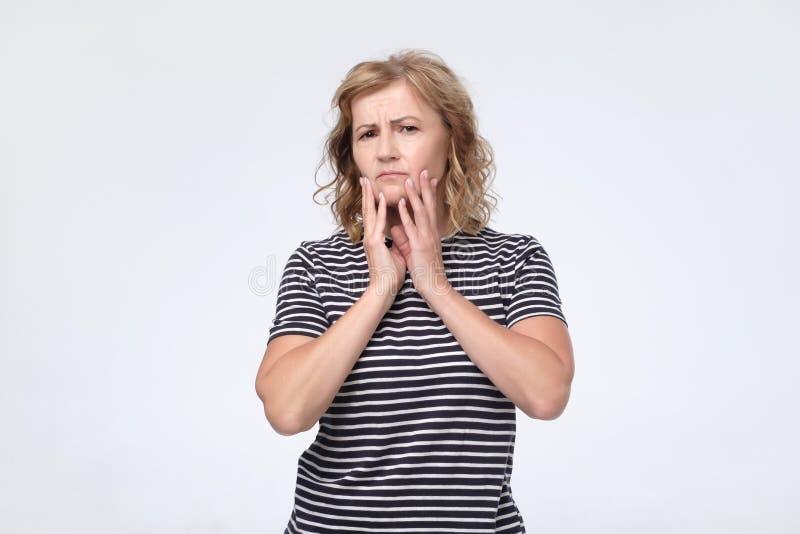 Misstänksam mogen kvinna som visar misstrogen blick på studion royaltyfria bilder