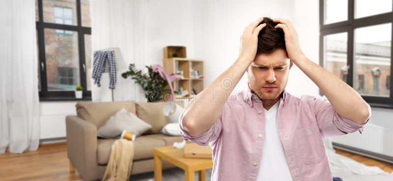 Misströstad ung man i smutsigt rum som har huvudvärk royaltyfri fotografi