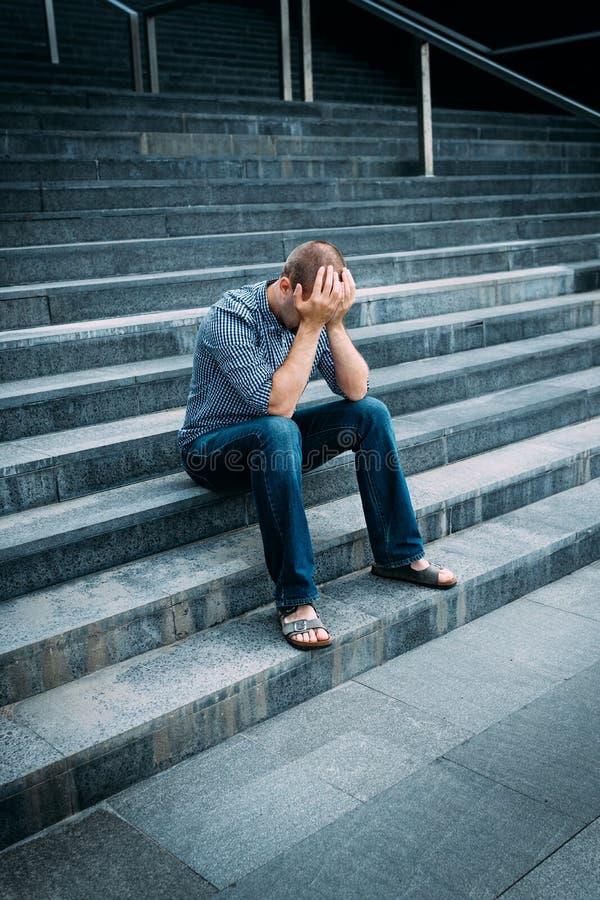 Misströstad ung man som täcker hans framsida med händer som sitter på trappa royaltyfria foton