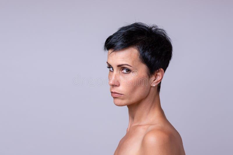 Misstrauische Frau, die seitlich der Kamera betrachtet stockbilder