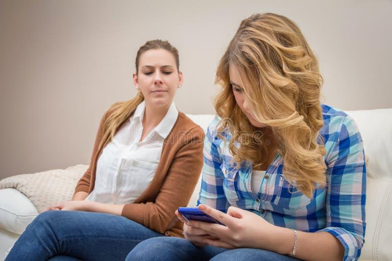 Misstrauische Mutter, die eine Tochter schaut Telefon ausspioniert lizenzfreie stockbilder