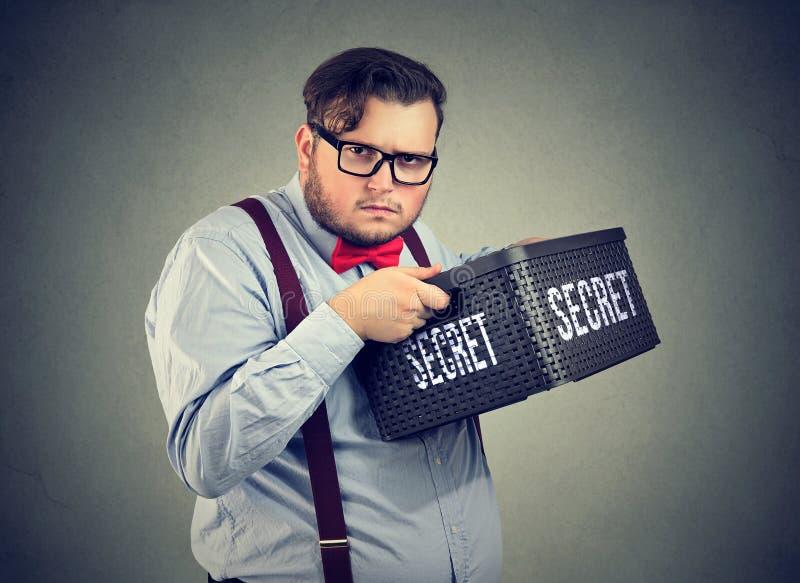 Misstrauischer Geschäftsmann, der Geheimnisse hält stockbild