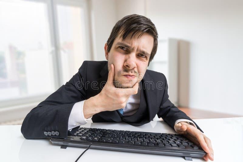 Misstrauischer Mann arbeitet mit Computer und schaut auf Schirm lizenzfreies stockbild