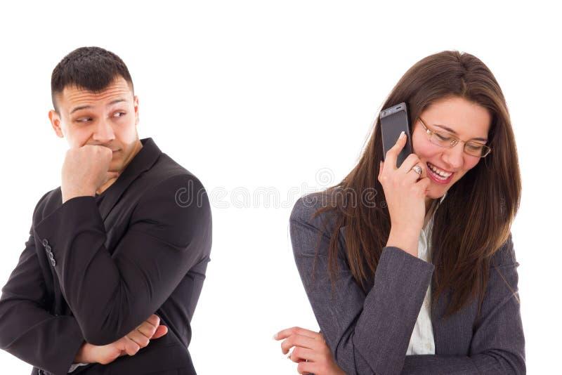 Misstrauischer Mann, der seine Frau spricht am Telefon betrachtet lizenzfreie stockfotos