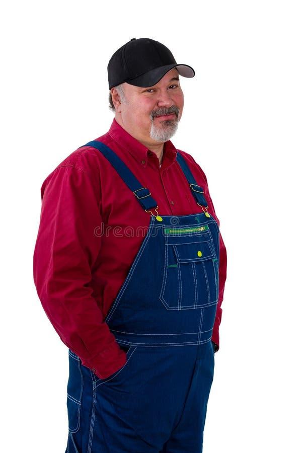 Misstrogen man på overaller med en tvivelaktig blick arkivfoto