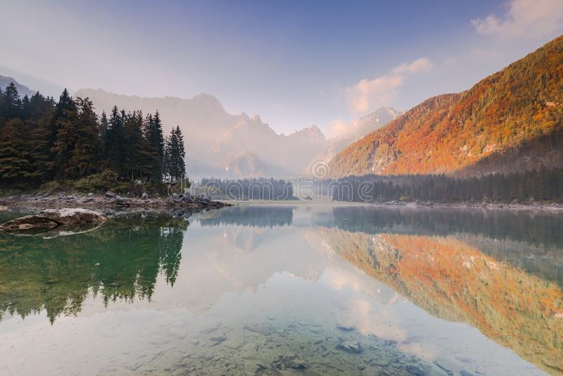 Mist at alpine lake with atumn colors in forest stock images