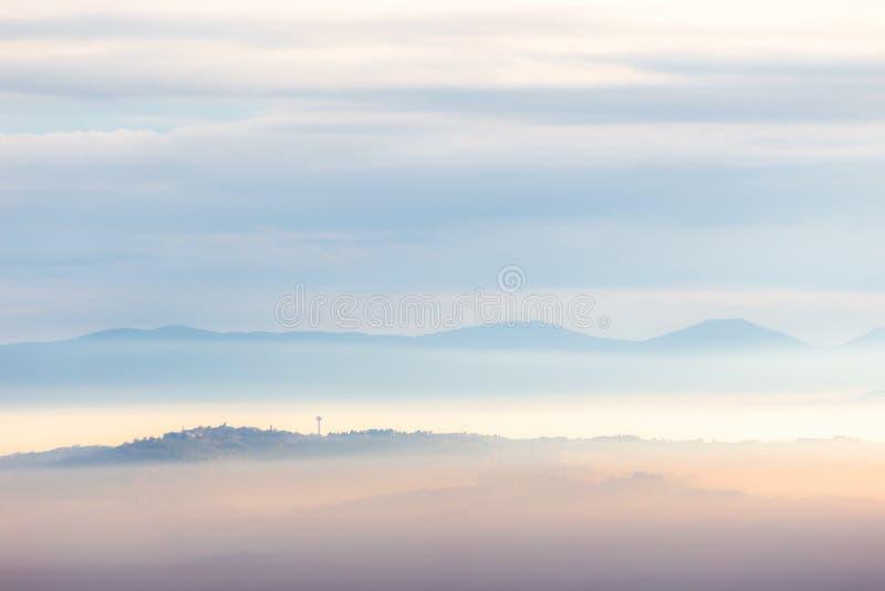 Mist die een vallei in Umbrië, Italië, met bergen en heuvels vult stock afbeelding
