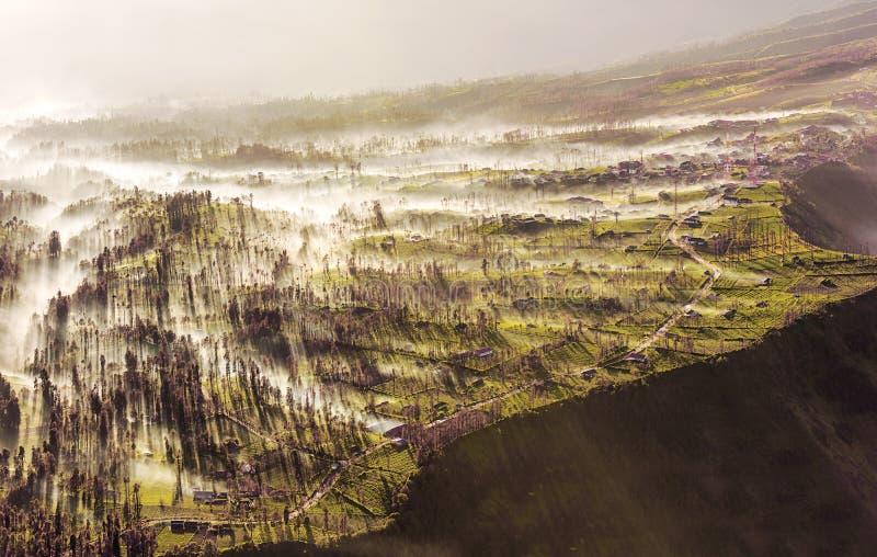 Mist die die over het dorp van Cemoro Lawang in de ochtend stromen aan ten noordoosten van MT Bromo, Indonesië wordt gevestigd royalty-vrije stock afbeelding