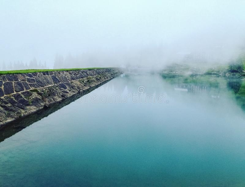Mist and fog over a lake on a winter day in a humid forest, film grain added stock photography