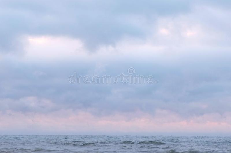 Mist and fog over the sea. Beautiful seascape with pink sunset and blue clouds. stock photo