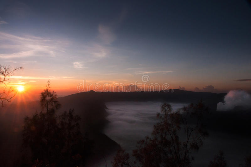 Mist hovering towards the active volcano Bromo in the morning during orange sunrise, at the Tengger Semeru National Park. Mist hovering towards the active stock image