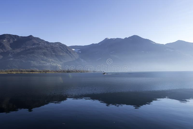 Mist on the lake, sharp steep mountains and reflections stock photos