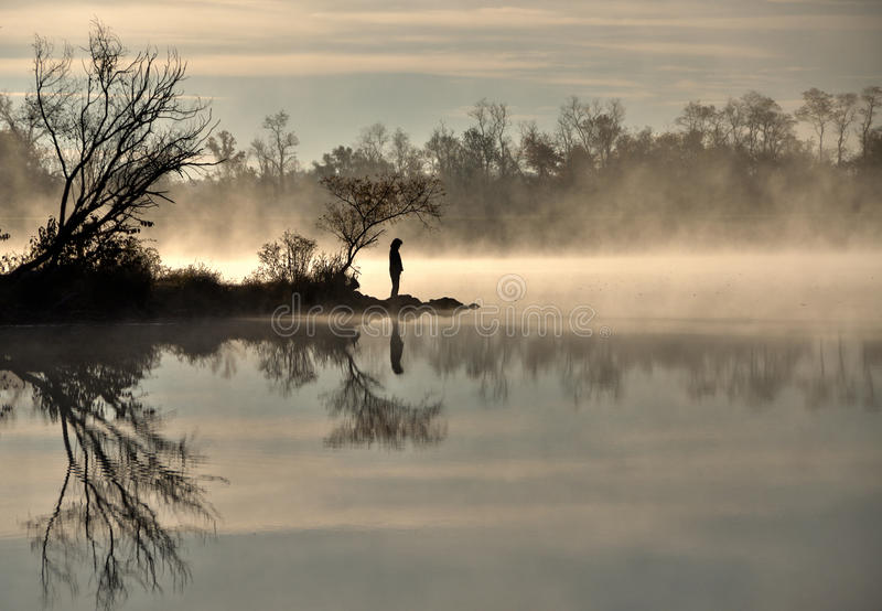 Mist on the lake at sunrise. A solitary silhouetted figure stands next to a quiet mist covered lake at sunrise, at Centennial Lake in Columbia Maryland