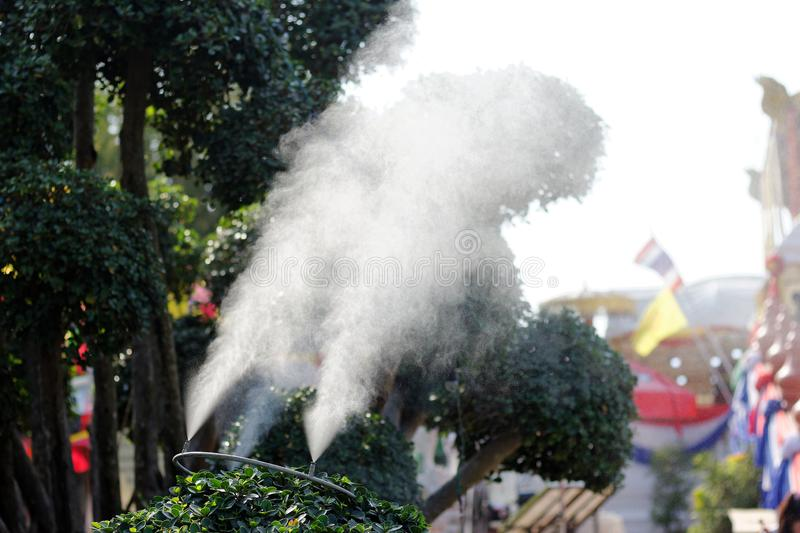 Mist nozzle sprays cold water create mist on a hot day,open air cooling system on summer stock photo