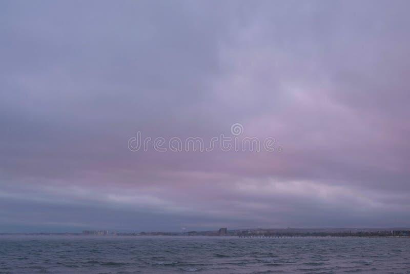 Mist och dimma över havet Härlig seascape med rosa solnedgång och kuststaden arkivbilder