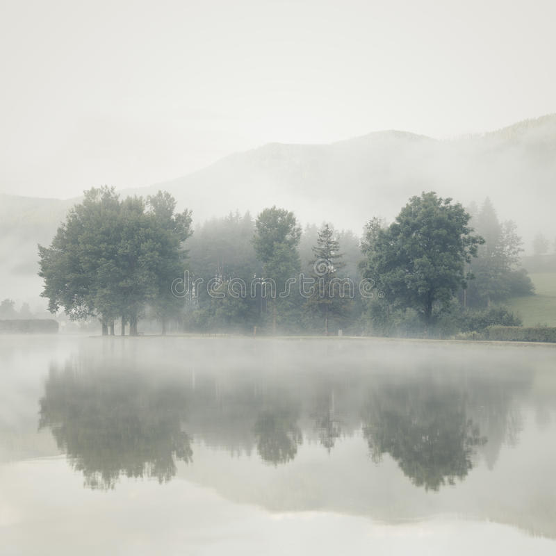 Free Mist On A Lake At Dawn With Trees And Mountains Reflected In The Royalty Free Stock Image - 75086526