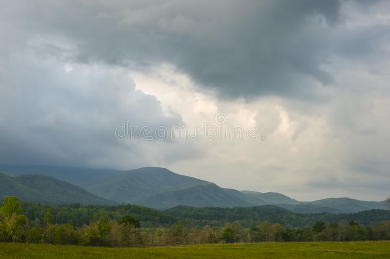 Cades Cove Mountain in gathering storm at the Great Smoky Mountains National Park, Townsend, TN. Mist rises from the mountains and storms gather in the sky at stock photography