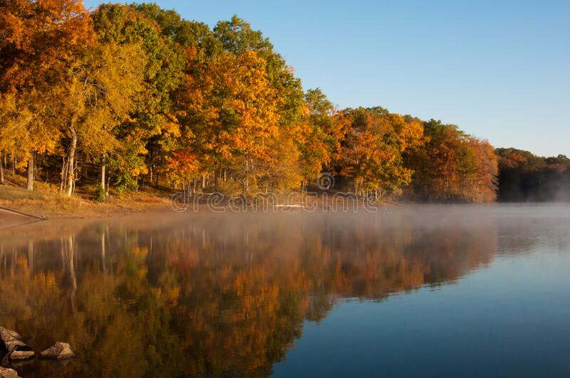 Mist rolls in and rises up to meet the brilliant autumn colors stock photo