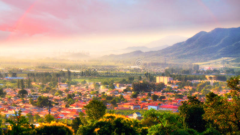 Mist village morning with rainbow, china. Village among mountains, foggy sunrise and rainbow in sky, Beijing suburbs district royalty free stock images