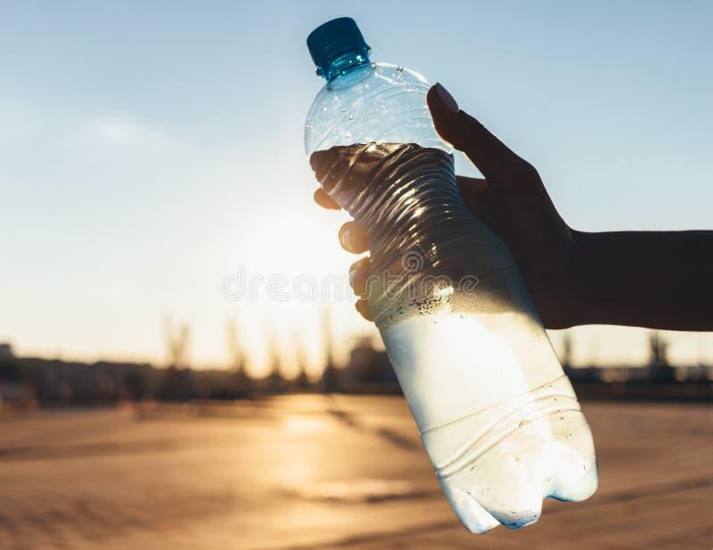 Misted flaska av kallt vatten i kvinnas hand arkivbild