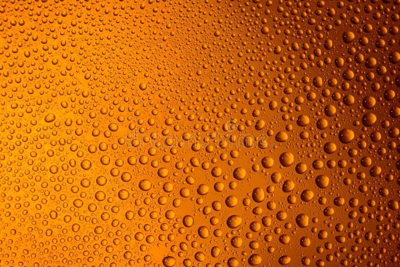 misted Glas Bierabschluß herauf einen orange hellen Hintergrund stockfotos