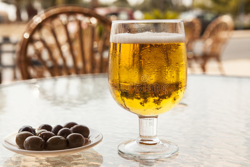 Misted glass of beer with olives on a glass table stock photography