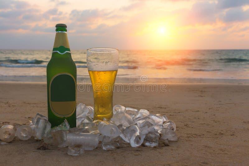 Mistedfles en glas koud bier op het zand van toneel bij de achtergrond van zeegezicht, zonsonderganghemel en overzeese golven stock afbeelding