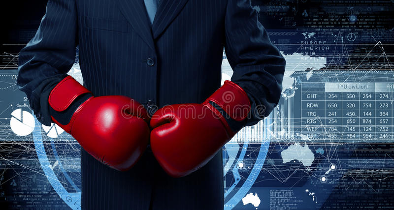Mister boss ready to fight . Mixed media. Determined businessman in suit and boxing gloves against graphs background royalty free stock photos