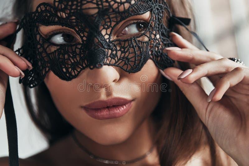 Misterio en ella Mujer joven atractiva que lleva una máscara negra y imágenes de archivo libres de regalías