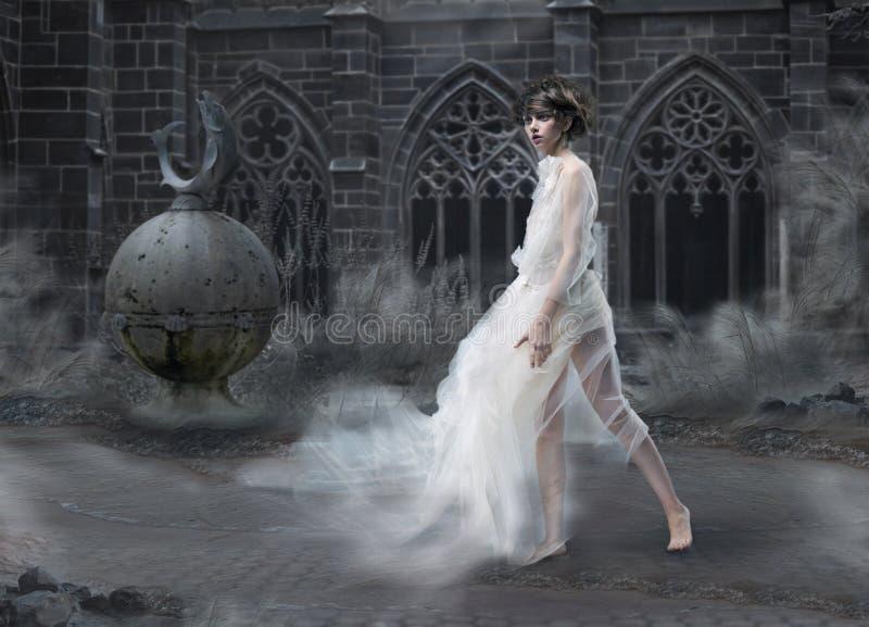 Misterio. Silueta mágica de la mujer en castillo ahumado viejo. Escénico antiguo místico foto de archivo