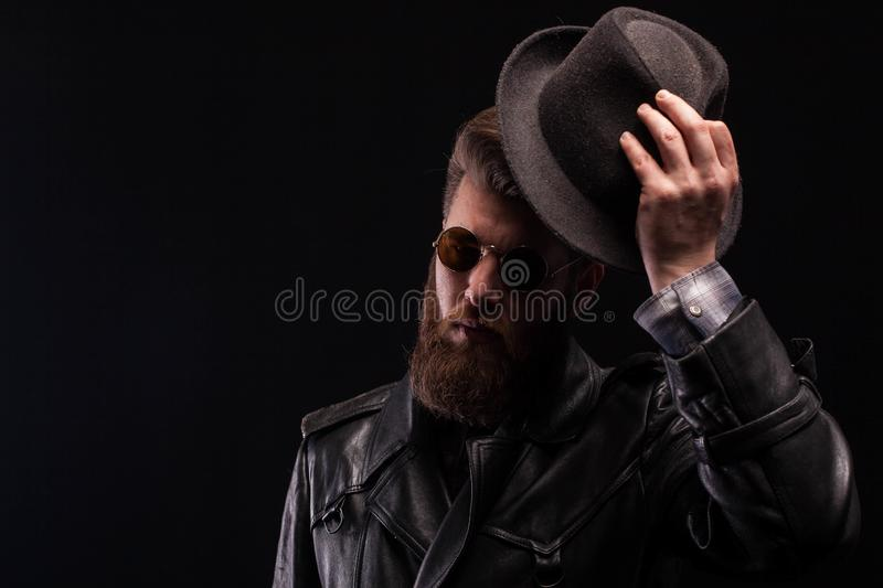 Misterious handsome bearded man with half of his face in the shadow while holding his hat over black background. Attractive man royalty free stock image