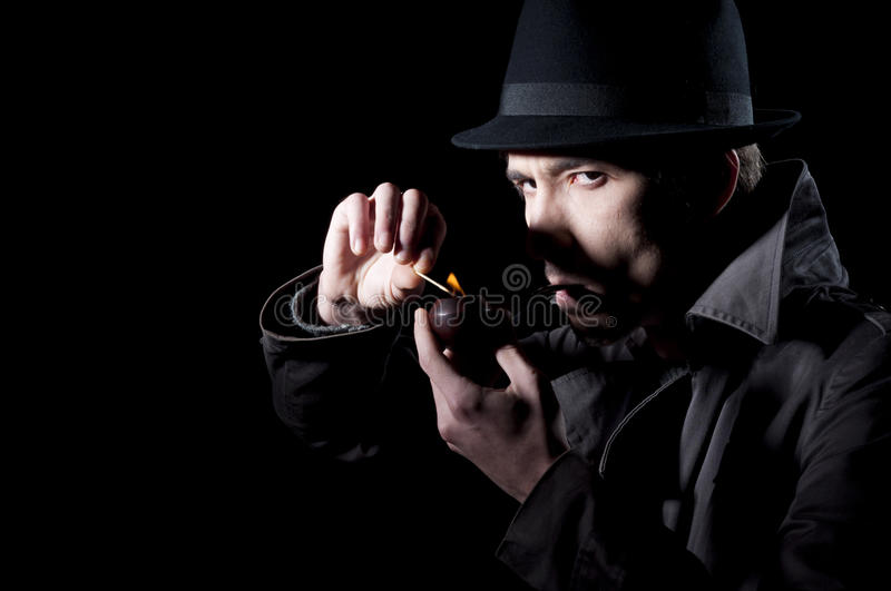 Mistery man. Private detective lighting his pipe, isolated on a black background royalty free stock photography