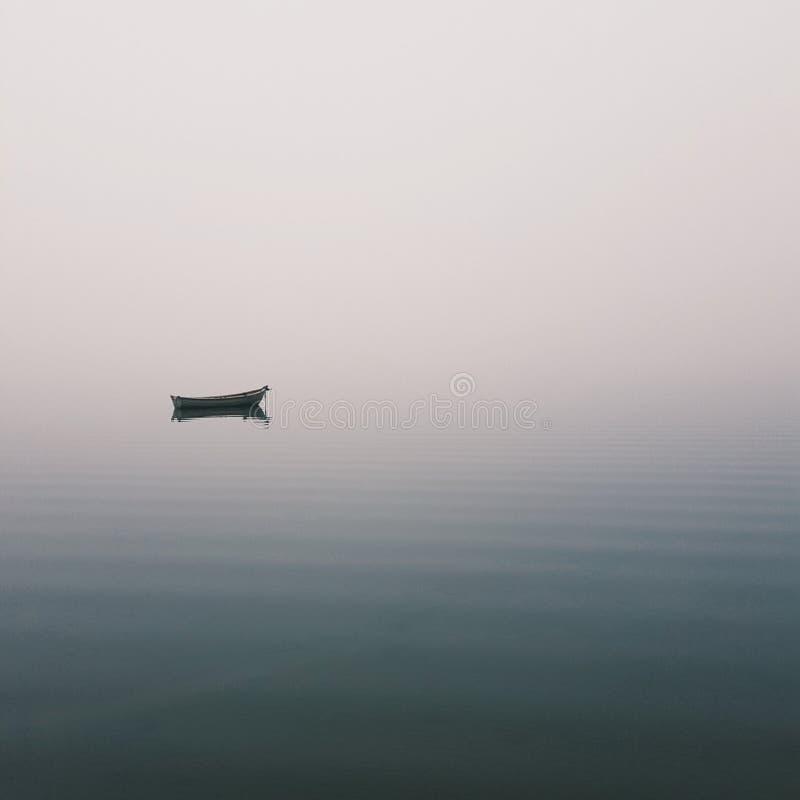 Mistic ensamt fartyg i mitt av sjön, mistdimma royaltyfri foto