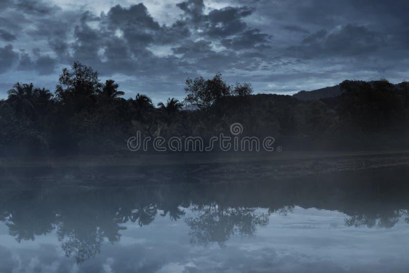 Mistig meer bij nachtachtergrond royalty-vrije stock fotografie