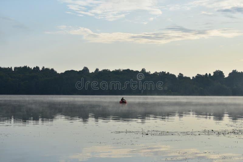 Mistige dageraad op de rivier, een eenzame visser van een boot die, weerspiegeld bos en wolken vissen stock foto's