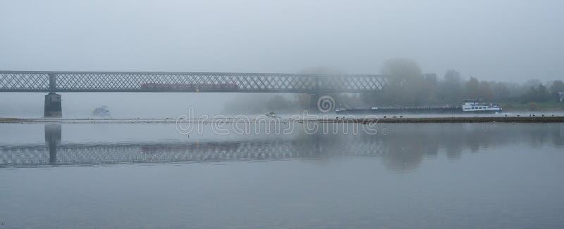 Mistige de herfstochtend in Duitsland op de rivier Rijn, een stromende aak in de afstand een oude spoorwegbrug stock afbeeldingen
