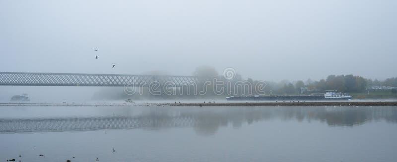 Mistige de herfstochtend in Duitsland op de rivier Rijn, een stromende aak in de afstand een oude spoorwegbrug royalty-vrije stock foto