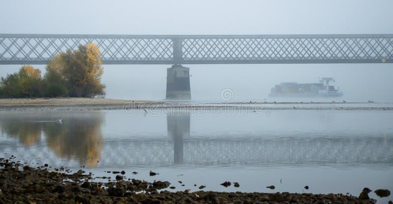 Mistige de herfstochtend in Duitsland op de rivier Rijn, een stromende aak in de afstand een oude spoorwegbrug royalty-vrije stock foto's