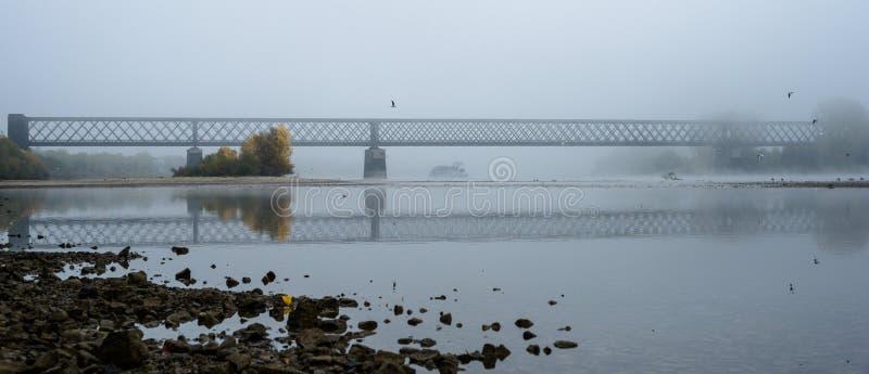 Mistige de herfstochtend in Duitsland op de rivier Rijn, een stromende aak in de afstand een oude spoorwegbrug royalty-vrije stock afbeelding