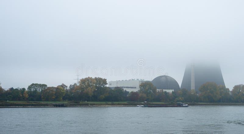 Mistige de herfstochtend in Duitsland op de rivier Rijn, een stromende aak Zichtbare schoorsteen van een kernenergieinstallatie i royalty-vrije stock fotografie